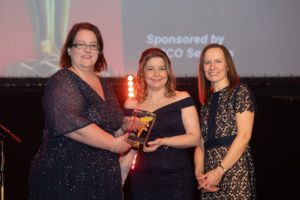 Liniar Group Finance Director Monika Bailey and Financial Controller Andrea O'Donnell receive the award from Emma Phillips